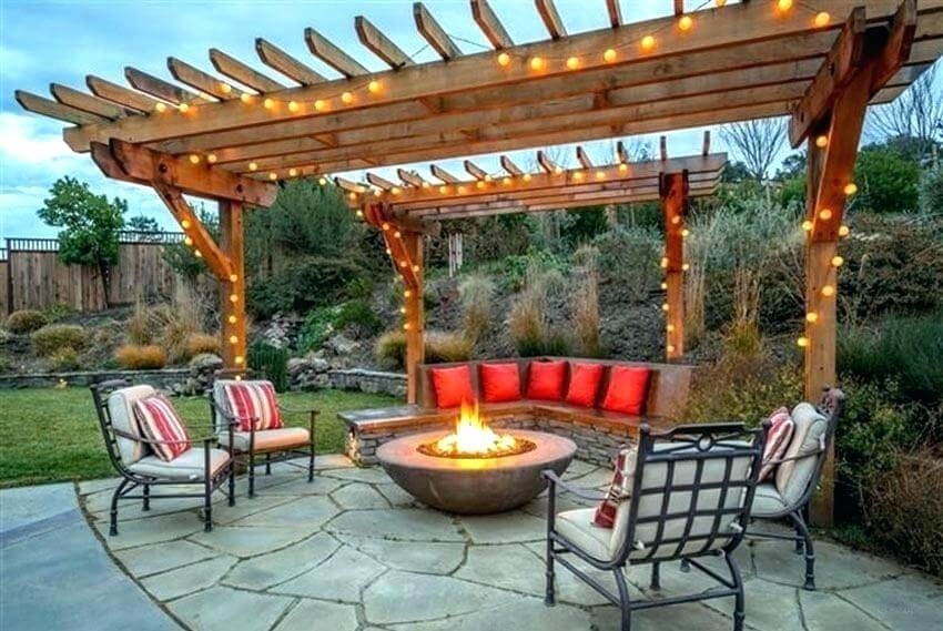 wooden pergola with lights and firepit